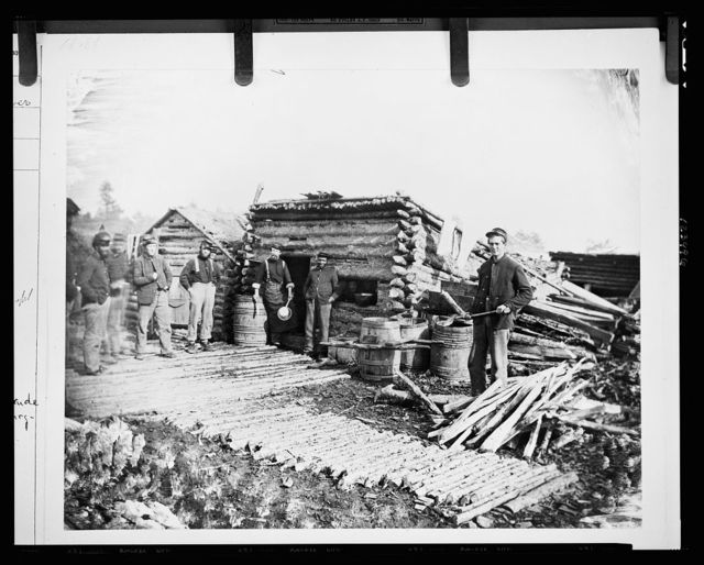 [Civil War camp of the 6th N.Y. Artillery at Brandy Station, Virginia, showing Union soldiers in front of log company kitchen]
