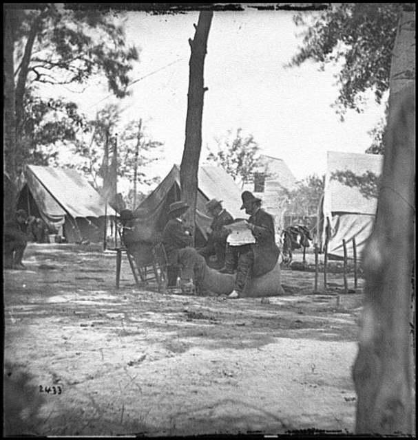 [Gen. Ambrose E. Burnside (reading newspaper) with Mathew B. Brady (nearest tree) at Army of the Potomac headquarters]
