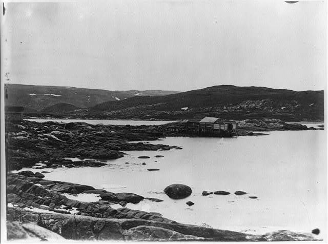 [Harbor on the coast of Labrador, with two wooden buildings on the rocky shore]