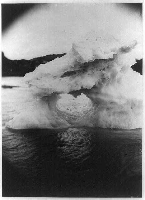 [Iceberg or ice formation with hole at center, off the coast of Labrador, with land visible in the background]