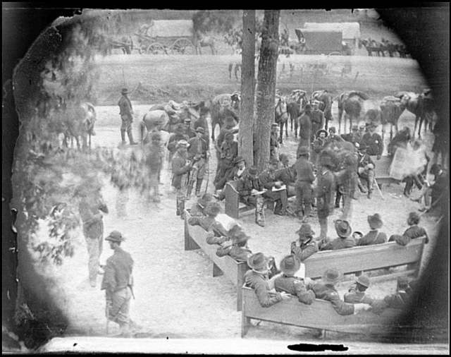 "[Massaponax Church, Va. ""Council of War"": Gen. Ulysses S. Grant (left end of bench nearest tree) writing a dispatch]"
