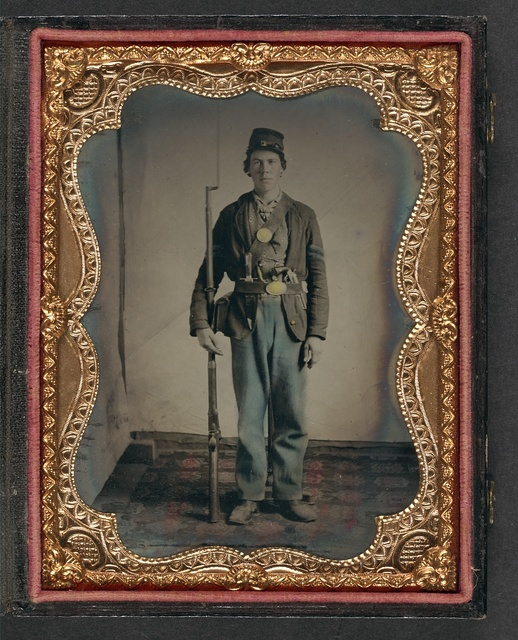 [Private Hiram M. Kersey, 44th Iowa Infantry regiment, standing on rug with bayonet, knife, revolver, and cartridge box]
