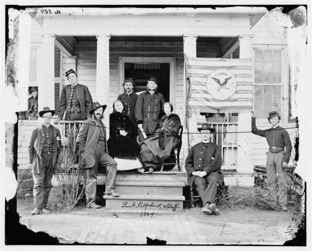 [Stevensburg, Va.  Gen. Judson Kilpatrick, 3d Division, Cavalry Corps, with ladies and staff members on the porch of headquarters]