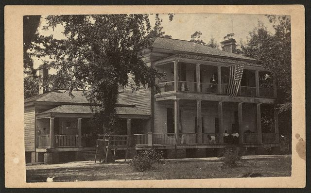 [Two-story building with U.S. flag flying from second floor, possibly used as Freedmen's quarters] / J. D. Heywoods photographic rooms, Craven St., 3d door South PO, New Berne, N.C.