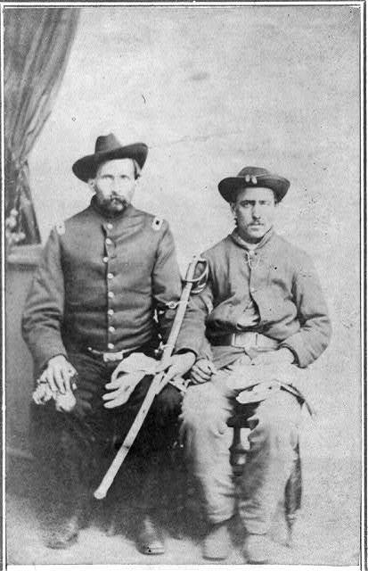 [Two unidentified Civil War soldiers in Union uniforms, seated in a photographer's studio; one is holding a saber]