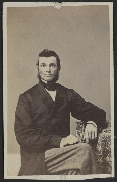 [Unidentified man seated at table] / J. St. John, photographer and dealer in photographic albums, and oval rosewood and gilt frames, Elkhorn, Wisconsin.