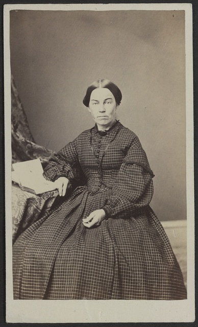 [Unidentified woman seated at table] / J. St. John, photographer and dealer in photographic albums, and oval rosewood and gilt frames, Elkhorn, Wisconsin.