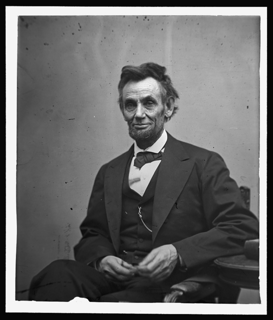 [Abraham Lincoln, three-quarter length portrait, seated and holding his spectacles and a pencil]