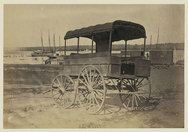 [Covered wagon with side curtains rolled up at a military facility]