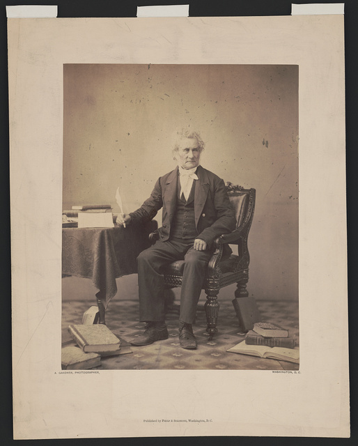 [Peter Force, full-length portrait, seated at table, facing slightly right, holding a quill pen in his right hand, with books on table and floor] / A. Gardner, photographer, Washington, D.C.