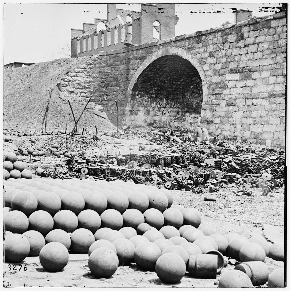 [Richmond, Va. Piles of solid shot, canister, etc., in the Arsenal grounds; Richmond & Petersburg Railroad bridge at right]