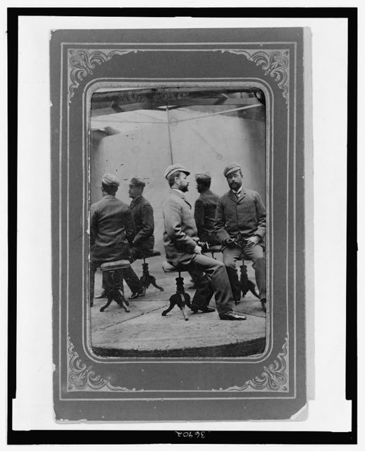 [Unidentified man in a studio photograph seated before two mirrors placed at right angles to provide five images]