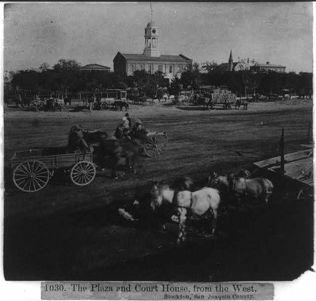 Wagon teams parked on the Plaza with Court House in background, from the West, Stockton, San Joaquin Co.