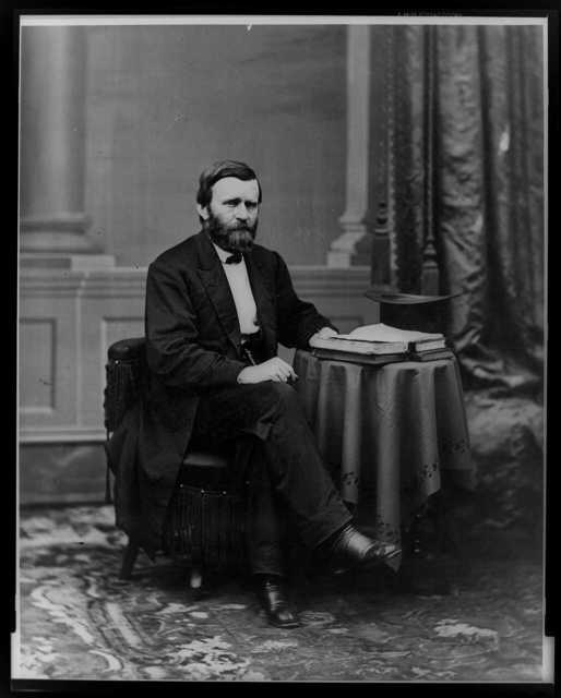 [Ulysses S. Grant, full-length portrait, seated at table with books and top hat, facing right]