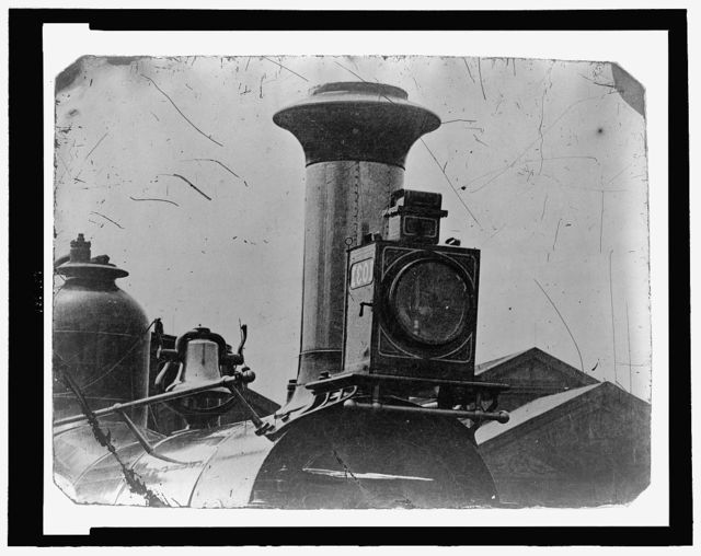 [Close up view of front of locomotive, showing light, smoke stack and bell]