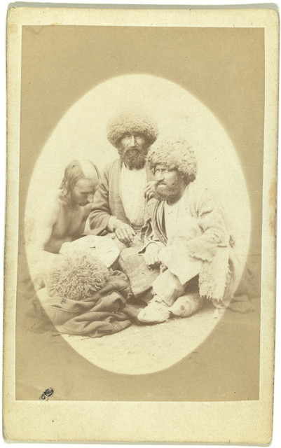 [Full-length portrait of three men, seated on ground, facing front]