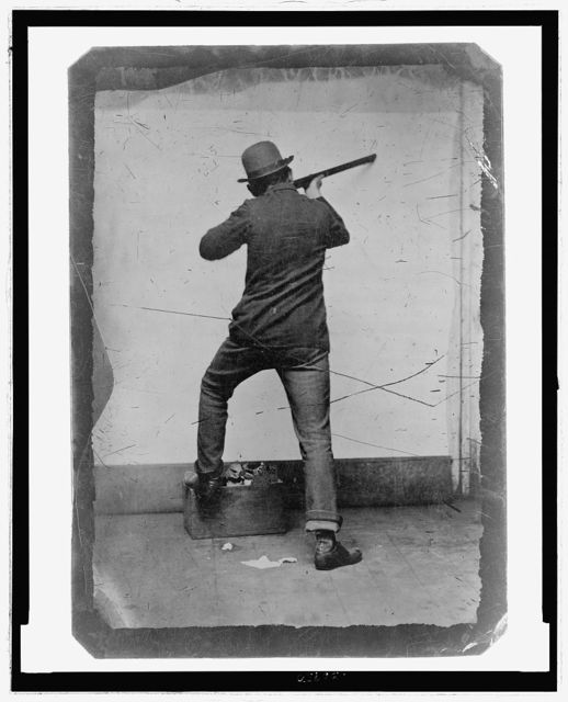 [Full-length rear view of a man posed as if shooting a rifle]