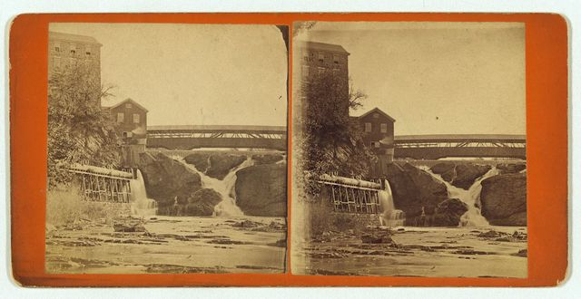 [Industrial building by waterfall with covered bridge spanning the falls]