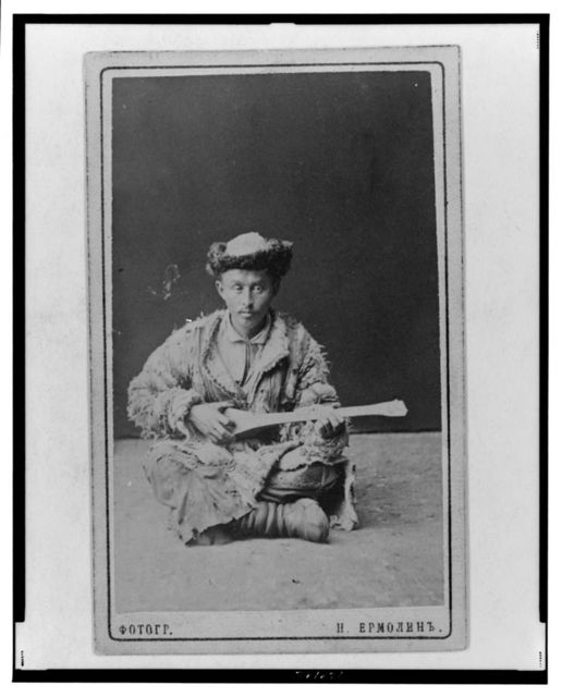 [Kazakh man, a musician with a dombra, seated]
