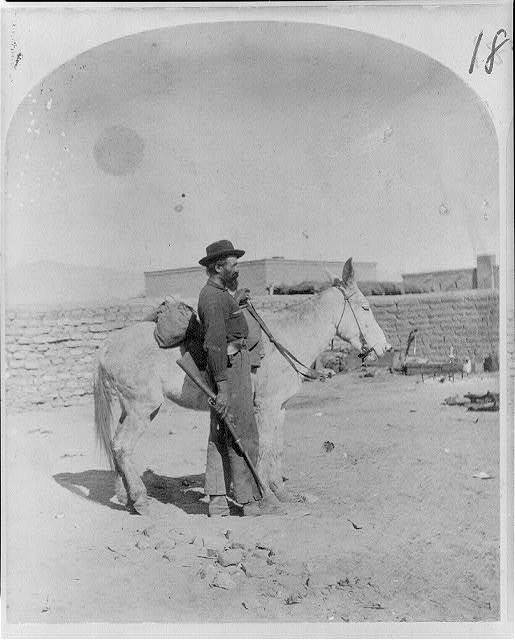 [Man with a rifle stands by the donkey facing right.]