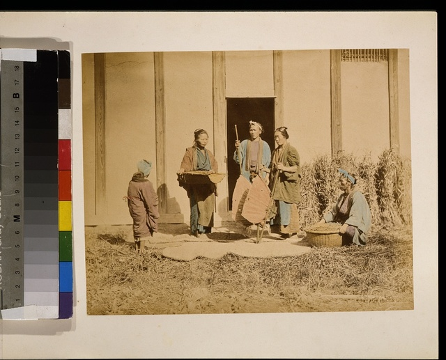[A group of people, possibly street vendors or farmers, two men and two women, two are holding baskets, and one person with back to camera may be a woman]