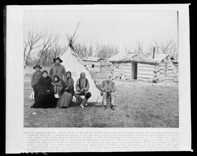 Enoch W. Raymond, wife, and other family members of wife's in front of teepee with log houses in background, Rose Bud Agency, South Dakota