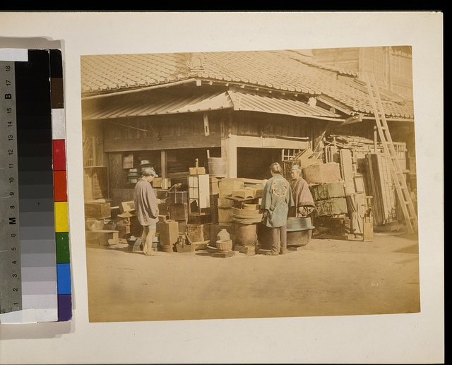 [Exterior view of store on the corner of the street with merchandise along the street sides and three people, shoppers and merchant(?), and a ladder leaning against the roof on the right]