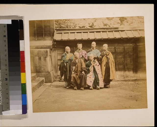 [Six men, possibly monks, posed for group portrait, four standing and two sitting in front, five have their heads shaved, wearing geta, some are holding items, with building in background]