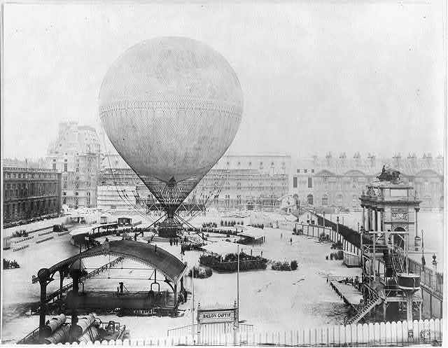 [Grand Balloon... de Mr. Henry Giffard, 1878 -  Birds-eye view of Balloon before ascent from Tuillerie Gardens, Paris; large crowd and reviewing stands]