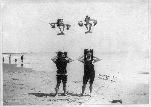 2 women standing on shoulders of 2 men on beach, R.I.?