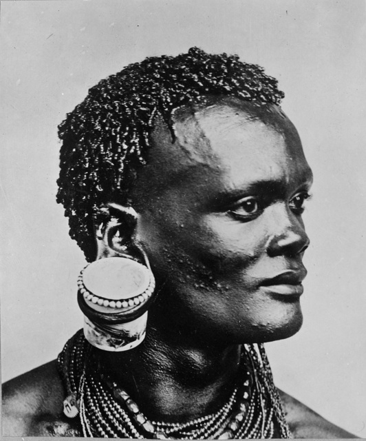 [Bust portrait of African man with jam pot hanging from his ear, Kenya]