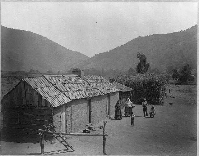 Digger Indian family in front of adobe building and bough wigwam on reservation, Tejon Ranch