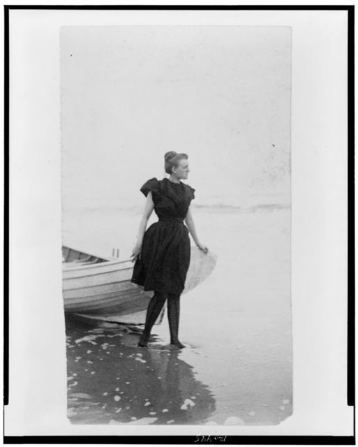 [Frances Benjamin Johnston, full-length portrait, standing at edge of ocean, in bathing suit, with left hand on boat, facing right]