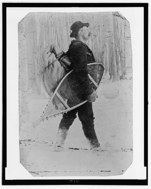 [Full-length portrait a man carrying a bundle on his back and snowshoes under one arm, appearing to walk through a snowy landscape]
