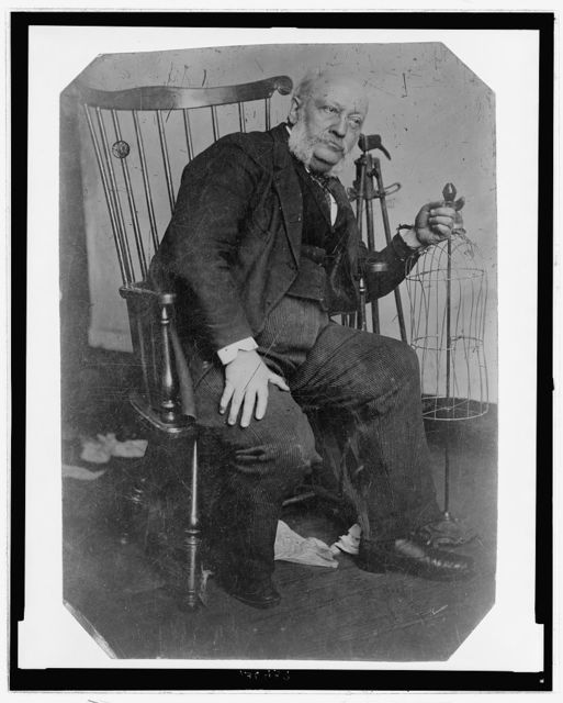 [Full-length portrait of a man, seated in a chair, leaning to one side with his left hand resting on a clothing frame(?)]