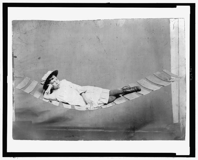 [Full-length portrait of a young girl reclining in a hammock]