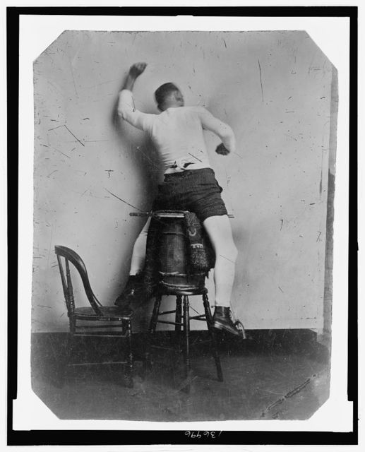 [Full-length rear view of a man seated on a barrel, gesturing as if riding a horse]