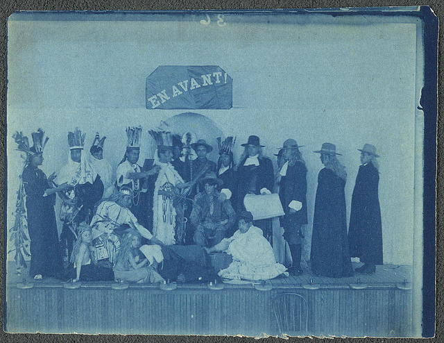 """[Pageant participants costumed as Pilgrims and Natives, posed beneath a banner """"En Avant!""""]"""