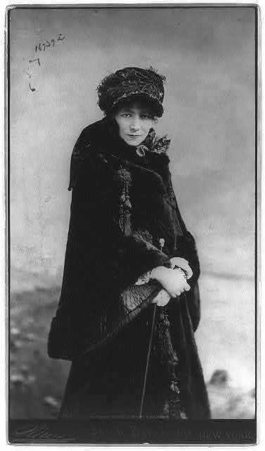 [Sarah Bernhardt, 1844-1923, three-quarters length portrait, standing, facing slightly right; wearing fur coat]