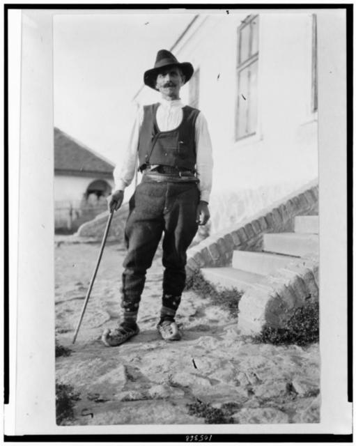 [Serbian man wearing hat, vest, belted pants, and pointed toed shoes with cane standing outside of building in Yugoslavia]