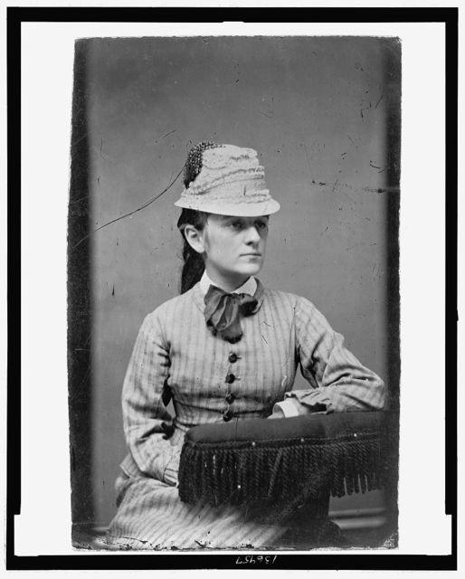 [Three-quarter length portrait of a woman seated, wearing a flower pot hat]