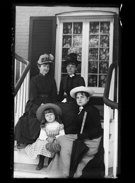 [Three women and a girl in hats, seated on steps of house]