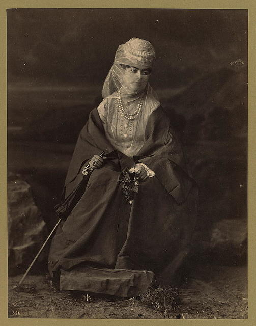 [Turkish woman, full-length portrait, seated, facing front, holding parasol and flowers]