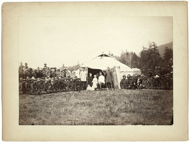 [Group of Kirghiz (i.e. Kazakh) men posing with a local Russian Governor, his wife, and their child in front of a yurt]