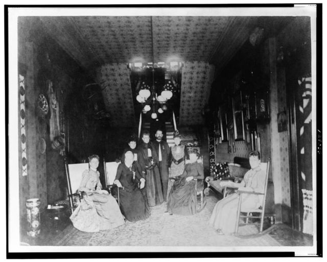[Mrs. Distin, Mrs. Conger, Mr. and Mrs. Bruce Goodfellow, Mrs. Logan, and Mrs. Lucket seated and standing in the stairhall of the John Alexander Logan home, Washington, D.C.] / from C.M. Bell's Photographic Studio, Washington, D.C.