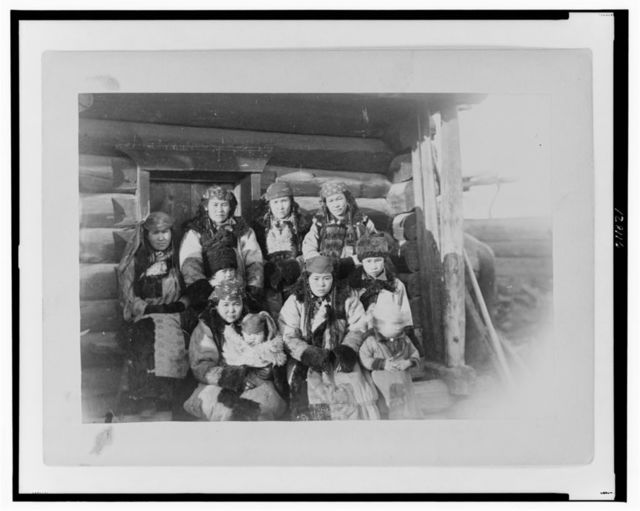 [Tatar women with children seated in front of their home]