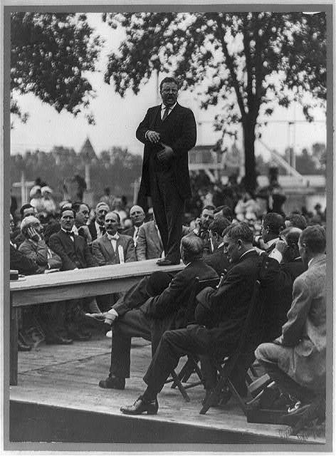 [Theodore Roosevelt standing on table outdoors and making speech to men seated around him, hands at waist] / Smith Art Photography, Freeport, Ill.