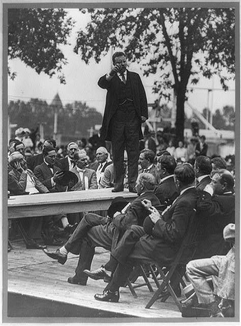 [Theodore Roosevelt standing on table outdoors and making speech to men seated around him, right hand raised] / Smith Art Photography, Freeport, Ill.