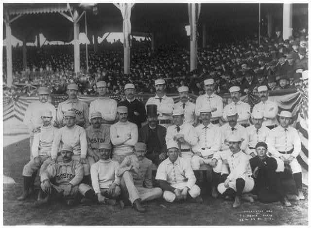 [Boston and New York players on opening day, 1886, at the Polo Grounds, 5th Ave. & 110th St., N.Y.C. posed in front of stands; Boston player in back rowon left has his middle finger raised in obscene gesture]