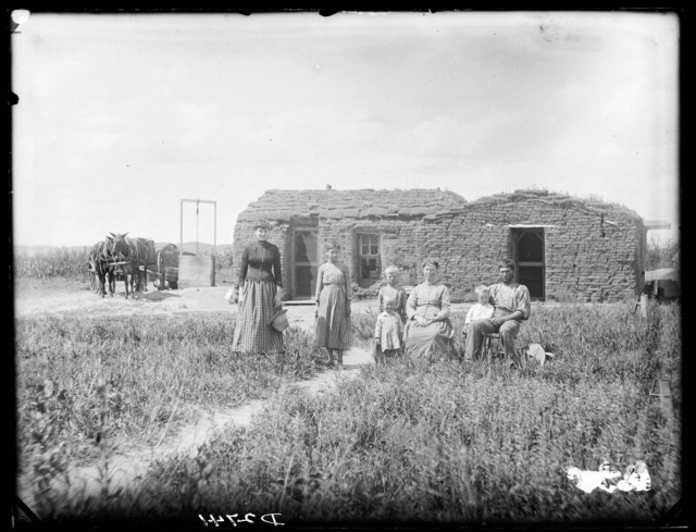 Family in front of the sod house of J.E. Evans, Sargent, Nebraska.